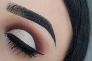 a woman with a red and pink cut crease eyeshadow look and dark insta brows, a popular brow trend